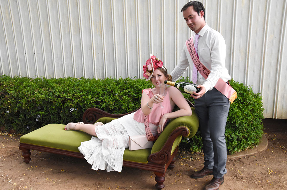 Elegant girl relaxing on green couch with man pouring her a champaign